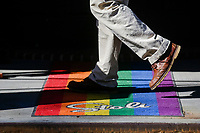 """NEW YORK, NEW YORK - MARCH 15: A man walks over a rainbow rug at Stonewall on March 15, 2021 in New York. With a """"Responsum ad dubium"""" the Catholic Church says that it does not bless same-Sex marriage.  (Photo by Emaz/VIEWpress)"""
