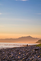 Hiker along a rocky beach in the Gulf of Alaska and Mt Fairweather of the Fairweather mountains.
