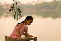 A young girl sits by Hoan Kiem Lake in Hanoi, Vietnam