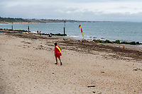 BNPS.co.uk (01202 558833)<br /> Pic: MaxWillcock/BNPS<br /> <br /> Pictured: An RNLI lifeguard walks across the empty beach with the mass of rotten seaweed.<br /> <br /> A south coast beach has become a no-go zone at the height of the summer holidays after a mass of rotten seaweed was allowed to fester on the sand.<br /> <br /> The vast carpet of kelp has been left to gather on Avon Beach in Christchurch, Dorset, for over a month.<br /> <br /> The unpleasant mess is attracting flies and is putting people off visiting the beauty spot which is normally hugely popular with families.<br /> <br /> Bathers are having to wade through the sticky seaweed to get to the sea and are usually left with their legs covered in it.