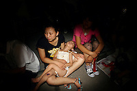 CHINA. Beijing. A child sleeps in the arms of her mother whilst watching the opening ceremony of the Beijing Summer Olympics. 2008