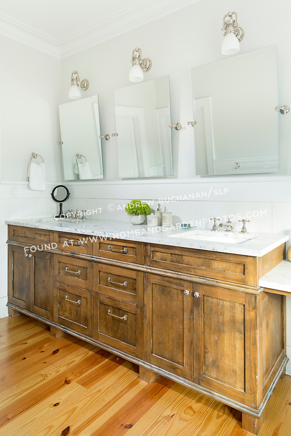 White marble counters complement the warm wood of the vanity in this bathroom.