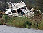 """John Pope (C) hands his wife Shirley Pope (R), of Pensacola, property they are salvaging from their 40 foot boat that landed on abandonded railroad tracks during Hurrican Ivan September 16,2004.  """"This is it,"""" said John Pope of what was left of his boat as he unloaded his belongings.  Son-in-law Chris Sterner (L) looks at other boats in Bayou Chico that were destroyed or damaged."""