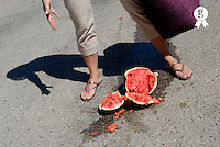 Woman standing by broken watermelon on asphalt, low section (Licence this image exclusively with Getty: http://www.gettyimages.com/detail/sb10065474bf-001 )