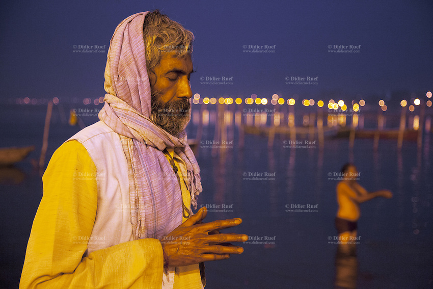 India. Uttar Pradesh state. Allahabad. Maha Kumbh Mela. An Indian Hindu devotee prays while another man takes a holy dip in Sangam at night. The man wears a scarf on his head. The Kumbh Mela, believed to be the largest religious gathering is held every 12 years on the banks of the 'Sangam'- the confluence of the holy rivers Ganga, Yamuna and the mythical Saraswati. In 2013, it is estimated that nearly 80 million devotees took a bath in the water of the holy river Ganges. The belief is that bathing and taking a holy dip will wash and free one from all the past sins, get salvation and paves the way for Moksha (meaning liberation from the cycle of Life, Death and Rebirth). Bathing in the holy waters of Ganga is believed to be most auspicious at the time of Kumbh Mela, because the water is charged with positive healing effects and enhanced with electromagnetic radiations of the Sun, Moon and Jupiter. The Maha (great) Kumbh Mela, which comes after 12 Purna Kumbh Mela, or 144 years, is always held at Allahabad. Uttar Pradesh (abbreviated U.P.) is a state located in northern India. 12.02.13 © 2013 Didier Ruef