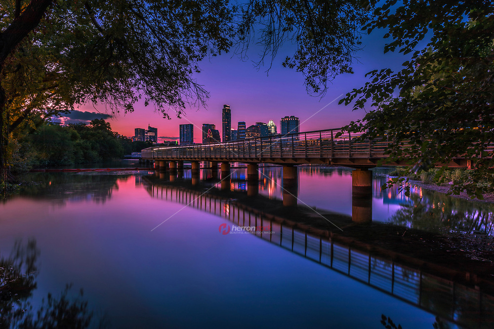 In this image depicting downtown Austin in its glory, a beautiful vibrant pink sunset falls on the Austin Skyline as seen from the the Boardwalk Trail at Lady Bird Lake.<br /> <br /> In the heart of Austin is the Ann and Roy Butler Hike-and-Bike Trail at Lady Bird Lake, a lush, urban path that meanders along the water's edge and passes by skyscrapers, neighborhoods, ball fields and cultural attractions.