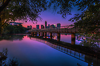 In this image depicting downtown Austin in its glory, a beautiful vibrant pink sunset falls on the Austin Skyline as seen from the the Boardwalk Trail at Lady Bird Lake.<br />