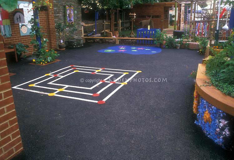 Children's garden at elementary school with vines, blacktop playground and games, plants