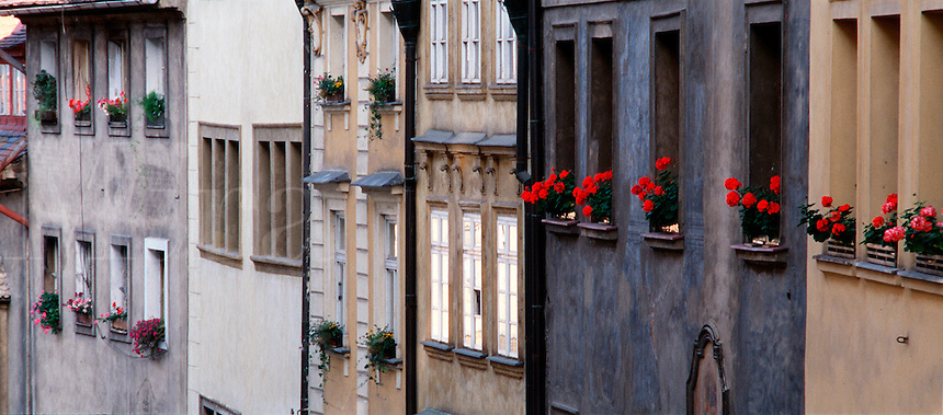 The exterior of old fashioned European row house buildings decorated with flowers in window boxes. Prague, Czech Republic.