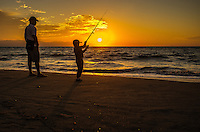 Sunset photograph of a little boy fishing in Puerto Vallarta as the sun sets on the ocean and father watches his son.