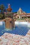 Monterey County, CA<br /> Courtyard fountain frames the cloister walk and tower of the Carmel Mission Basilica (1797) - Mission San Carlos Borromeo del Rio Carmelo
