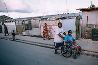 A man pushes his wheelchair-bound disabled relative along a street. Ebeye, one of the most densely populated islands in the world and is home to a large number of variously disabled people. Aside from the nearby nuclear testing sites, overcrowding, poor sanitation, and the failure of the US administration to immunise the population of Ebeye has meant that its residents has suffered a high degree of  diseases such as tuberculosis, polio, hepatitis, influenza, measles, cholera etc.