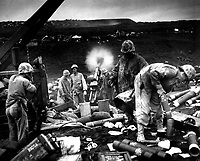 Across the litter on Iwo Jima's black sands, Marines of the 4th Division shell Jap positions cleverly concealed back from the beaches.  Here, a gun pumps a stream of shells into Jap positions inland on the tiny volcanic island. Ca. February 1945. (Coast Guard)<br /> Exact Date Shot Unknown<br /> NARA FILE #:  026-G-4122<br /> WAR & CONFLICT #:  1219