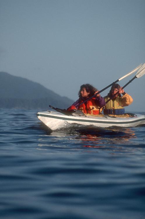 Sea kayakers, Couple in double kayak, Queen Charlotte Islands, British Columbia, Canada.