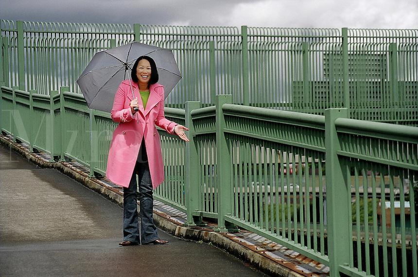 asian woman with umbrella enjoying break in the rain..MR