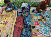 Rajasthan, India. Sawai Madhopur. Smiling local tribal women making traditional embroidered wall hangings.