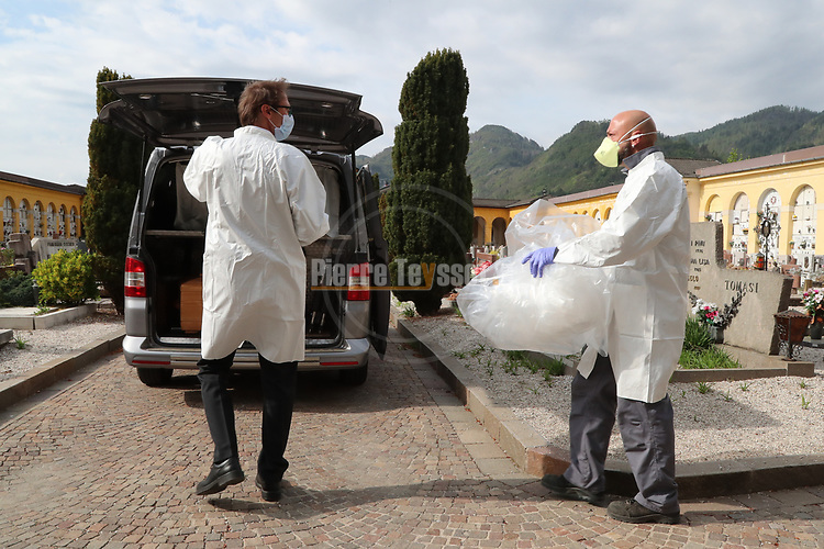 Europe Virus Outbreak - Cemetery Works in Pergine Valsugana, Italy on April 21, 2020. A sweeping lockdown is in place in Italy to try to slow down the spread of coronavirus pandemic. Employees wearing gloves and masks treat a coffin of a person who died of a heart attack.