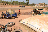 MALI, Kayes, Sadiola, water storing and filling station, water is stored in large plastic film bags for sale to small scale goldminers, transport in chinese three-wheeler APSONIC / Wassertankstelle, Wasserspeicher in grossen Säcken, Verkauf an Goldwäscher
