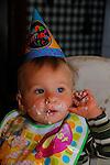 A one year old boy enjoying his birthday cake.