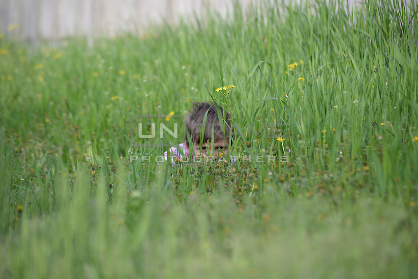A kid in hiding in a field near the railroad during a firefight. Slavyansk, Donetsk region.