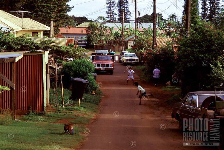 Boys playing catch in the streets of Lanai City, in the days when it was still a plantation town, Island of Lanai, Hawaii.