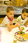 Education preschoool children ages 3-5 meal time lunch boys serving themselves from dish with chicken vegetables and cheese vertical