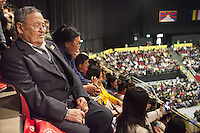 """Switzerland. Basel. St. Jakobshalle. A tibetan family seats among the crowded audience and listens to His Holiness the Dalai Lama during his public lecture on Training the Mind. The eight verses for Training the Mind deal with the practises associated with cultivating the method aspect or the path such as compassion, altruism, aspiration to attain buddhahood, and so on. The father is asleep and his daughter is taking a selfie with her mobile smartphone. The Tibetan flag, also known as the """"snow lion flag"""" and the 'Free Tibet flag', was a flag of the military of Tibet, introduced by the 13th Dalai Lama in 1912 and used for the same capacity until 1959. Designed with the help of a Japanese priest, it reflects the design motif of the Japanese military's Rising Sun Flag. Since the 1960s, it is used a symbol of the Tibetan independence movement. The flag of Switzerland consists of a red flag with a white cross (a bold, equilateral cross) in the centre. 7.02.2015 © 2015 Didier Ruef"""