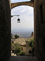 view through archway to Umbrian valley from the village of Assisi, Ital