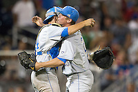 UCLA catcher Shane Zeile (14) hugs pitcher David Berg (26) immediately following Game 8 of the 2013 Men's College World Series the North Carolina State Wolfpack on June 18, 2013 at TD Ameritrade Park in Omaha, Nebraska. The Bruins defeated the Wolfpack 2-1, eliminating North Carolina State from the tournament. (Andrew Woolley/Four Seam Images)
