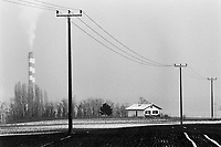 """Switzerland. Geneva. The chimney of  """"Les Cheneviers"""" which is the incinerating plant, distant 25 km from the town. Electric pylons in the countryside. A small private house in the middle of the agricultural fields. Winter season. Snow. © 1991 Didier Ruef"""