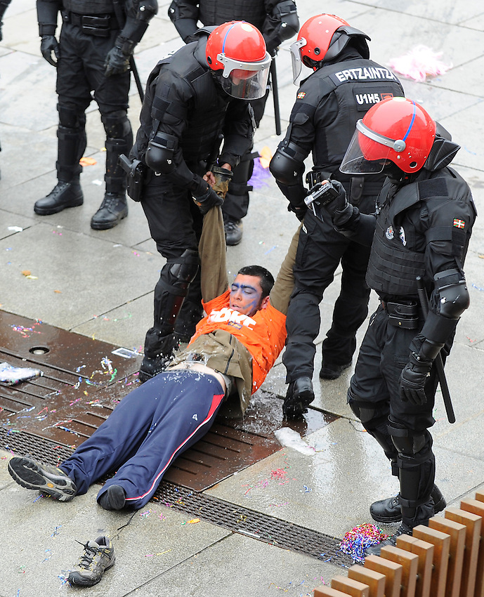 """Protesters wearing masks take part in a demonstration against the arrest of seven youths sentenced to six years in prison on charges of being members of the pro-independence Basque youth organization SEGI in Gasteiz on May 17, 2015. 4 of the 7 condemned youths were arrested by the police and the other 3 escaped. Igarki Robles, Aiala Zaldibar and Ibon Esteban have announced that they are taking part in this protest. Banner reads """"With disobedience, free"""". PHOTO: ANDER GILLENEA"""