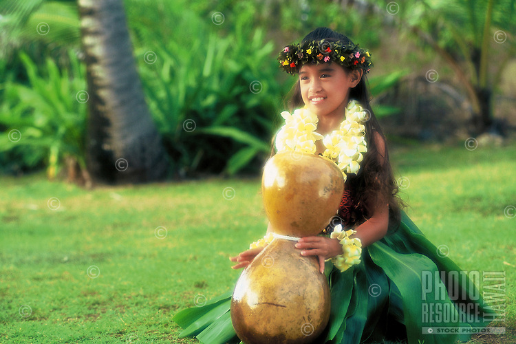 Beautiful young Hawaiian girl (age 7) with ipu heke (gourd), plumeria leis and ti leaf skirt performing a hula noho (seated hula)