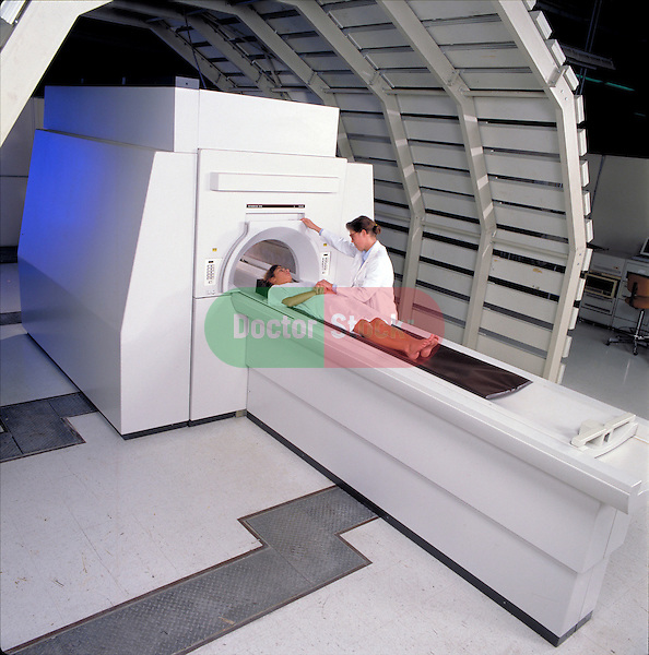 Technician preparing female patient for MRI procedure