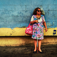 A blind woman, holding a white cane, waits for a bus in the backyard of San Miguelito public market in San Salvador, El Salvador, 10 April 2018.