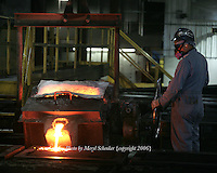 A worker at D & L Foundry in Moses Lake, Washington pours an iron mixture into manhole-cover molds on August 16, 2006. His gloves and protective suit are designed to insulate his hands, lower arms and body from temperature extremes and hot splashes fro molten metals or other hot liquids. He is also wearing a Class B hard hat, earplugs, and respirator.