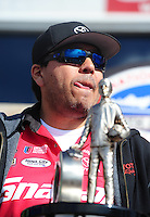 Nov. 13, 2011; Pomona, CA, USA; NHRA funny car driver Cruz Pedregon stands next to the championship trophy during the Auto Club Finals at Auto Club Raceway at Pomona. Mandatory Credit: Mark J. Rebilas-.