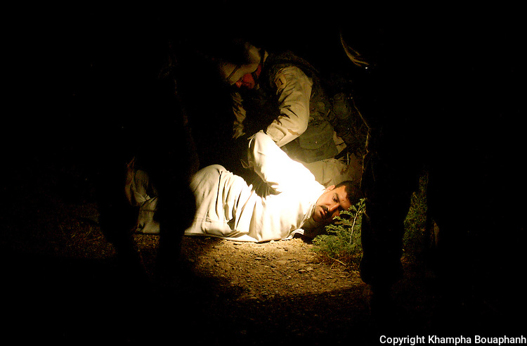 An insurgent is detained by U.S. soldiers near Kirkuk, Iraq on May 18, 2003.  (Photo by Khampha Bouaphanh)