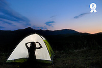 Silhouette of teenager girl (13-14) in illuminated tent, brushing hair (Licence this image exclusively with Getty: http://www.gettyimages.com/detail/sb10065474ai-001 )