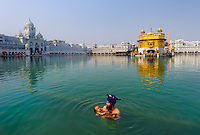 Amritasr, Punjab, India<br /> I was mesmerized by the love this father emanated for his child as he dipped his newborn in the Holy Pool of Nectar at the Golden Temple. The Golden Temple is the holiest shrine in Sikhism and a major pilgrimage for Sikhs from all over the world. Theirs is philosophy of generosity and these were some of the gentlest and kindest people I've met in India. Pilgrims purify themselves in the holy waters- the men are careful to tie their ever-present ceremonial daggers to their turbans for safekeeping as the women bathe modestly behind a wall.<br /> <br /> One of the many things I have learned during my years of global travel is that no matter how unique we may look in appearance, from the exotic to the mundane, we basically have the same universal desires and concerns. Our needs are actually quite simple: to love and be loved; to have a useful place in our society with some meaningful and fulfilling occupation in our life; work that will hopefully provide us with enough money in our pocket to get by; food on the table; education, health and safety for ourselves, our family and our children. The freedom to be ourselves is what connects us as a human race.<br /> <br /> This celebration of the spirit resides within us all. It is what bonds us as mankind, a continued thread, as together we continue on this journey in the pilgrimage of life.