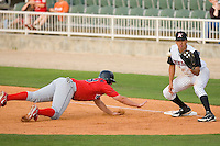First baseman Jose Vargas #39 of the Kannapolis Intimidators waits for the throw as Brendan Akashian #28 of the Lakewood BlueClaws dives back to the bag at Fieldcrest Cannon Stadium May 16, 2009 in Kannapolis, North Carolina. (Photo by Brian Westerholt / Four Seam Images)