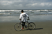 Santos, Sao Paulo State, Brazil. Man leaning on his bicycle on the beach, watching the sea, wearing a no. 10 football shirt.