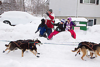 Saturday, March 3, 2012  Spectators wave as Anna Berington runs by them on Cordova street during the Ceremonial Start of Iditarod 2012 in Anchorage, Alaska.