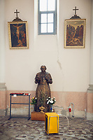 Switzerland. Canton Ticino. Barbengo. Church «San Carlo». Religious catholic paintings on the wall. Flowers pots and a heater. A man, who is a faithful coming every week to mass, offered to the church a bronze statue from Pope Saint John Paul II (Latin: Ioannes Paulus II; born Karol Józef Wojtyła; 18 May 1920 – 2 April 2005) who served as Pope of the Catholic Church and sovereign of Vatican City from 1978 to 2005. John Paul II is recognised as helping to end Communist rule in his native Poland and eventually all of Europe. John Paul II significantly improved the Catholic Church's relations with Judaism, Islam, the Eastern Orthodox Church, and the Anglican Communion. He upheld the Church's teachings on such matters as artificial contraception and the ordination of women, but also supported the Church's Second Vatican Council and its reforms. He was one of the most travelled world leaders in history, visiting 129 countries during his pontificate. As part of his special emphasis on the universal call to holiness, he beatified 1,340 people and canonised 483 saints, more than the combined tally of his predecessors during the preceding five centuries. 25.03.2018 © 2018 Didier Ruef