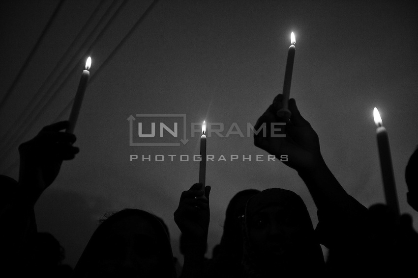 Bangladeshi garment workers and relatives of victims of the Rana Plaza building collapse hold candles during a memorial at the site of the Rana Plaza garment factory building collapse in Savar, on the outskirts of Dhaka on October 24, 2013, the six-month anniversary of the disaster. Savar, near Dhaka, Bangladesh