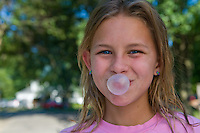 Young girl, 10-15, with blue eyes and blonde hair blows a bubble with gum.