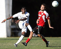 Kofi Sarkodie #8 of the University of Akron sends the ball past Nick DeLeon #14 of the University of Louisville during the 2010 College Cup final at Harder Stadium, on December 12 2010, in Santa Barbara, California.Akron champions, 1-0.