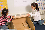 Preschool  horizontal 4-5 year olds block area two girls working together to position long block