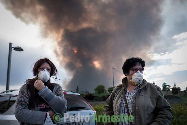 Two neighbours of Sesena wear masks as they wait for other relatives to evacuate a residential area affected by th toxic fumes produced by tyres burning in an uncontrolled dump near the town of Sesena, after a fire broke out early on May 13, 2016. A huge tyre dump near Madrid was ablaze today, releasing a black cloud of toxic fumes and forcing the evacuation of nearby residents after what officials suspect was an arson attack.  © Pedro ARMESTRE