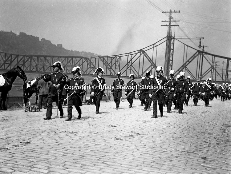 Pittsburgh PA:  Pittsburgh-area Manson marching in the annual St Patrick's Day Parade.  View of Homer Stewart and fellow Masons marching down Water Street with the Wabash Bridge in the background