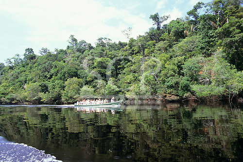 Amazon, Brazil. Tourists in an open motor canoe on an ecotourism expedition into the rainforest. Ariau Tower Hotel, Amazonas.